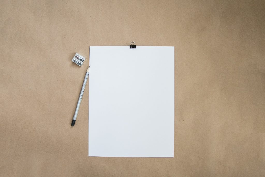 Blank sheet of paper and a pencil on a desk